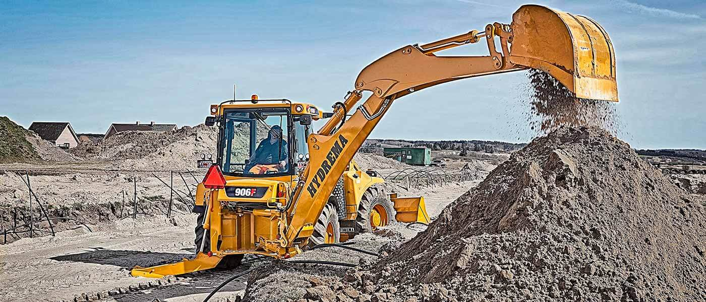 Hydrema 906F backhoe loader digging with it