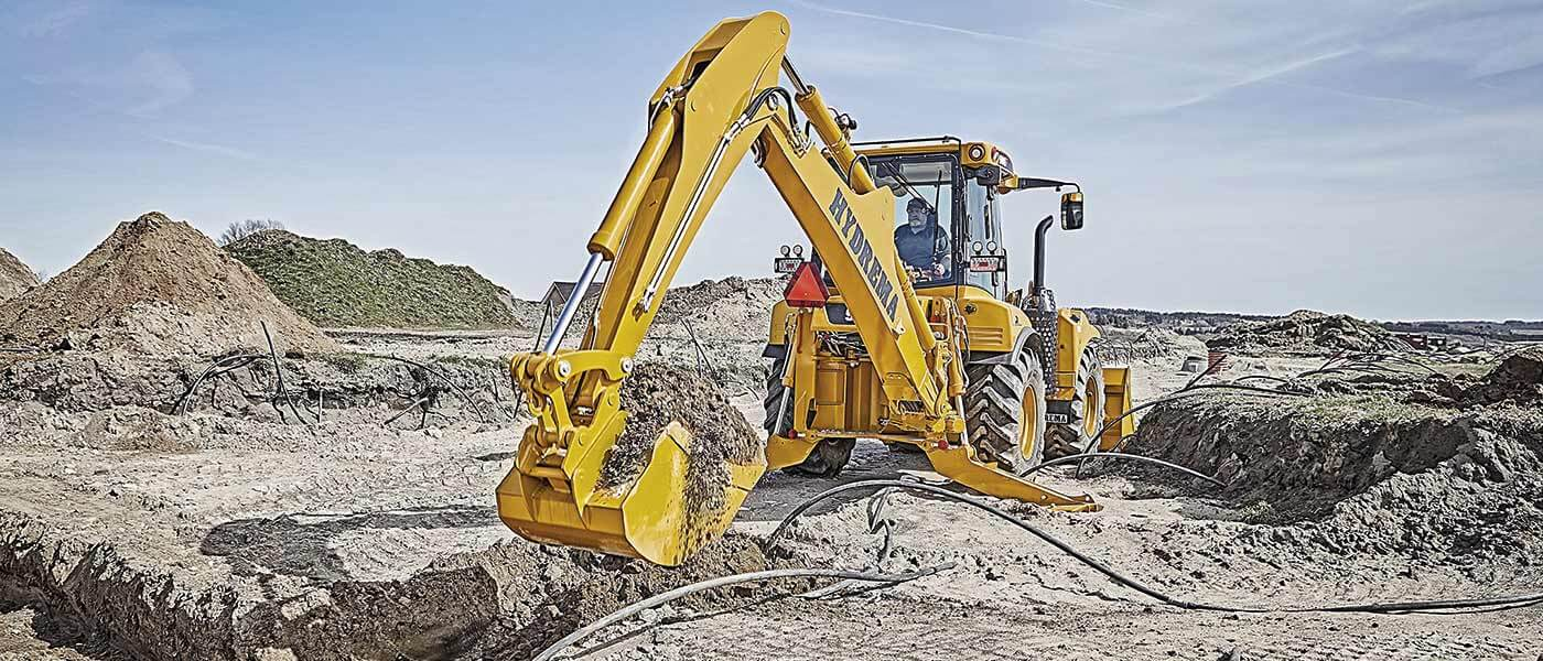 Hydrema 906F backhoe loader digging cabels into the ground with it